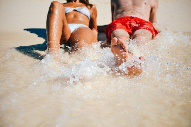 Muž a žena ležiac na pláži s nohami namočenými v mori