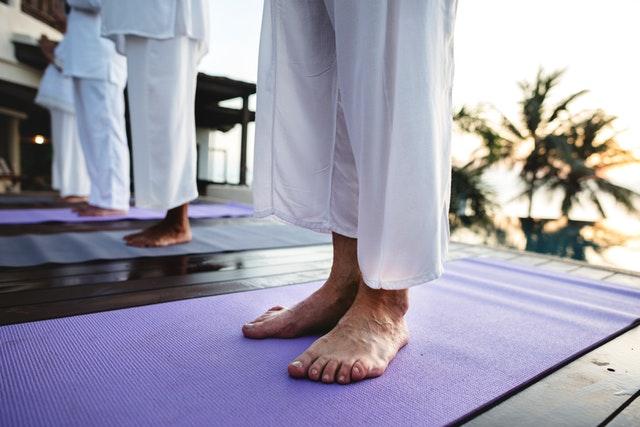 Ľudia s bosými nohami, ktorí cvičia yougu na podložkách