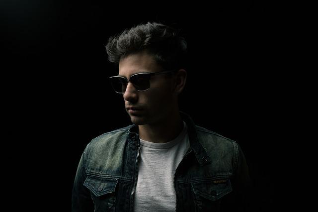 Muž v slnečných okuliaroch v rifľovej bunde s čiernymi vlasmi.jpg