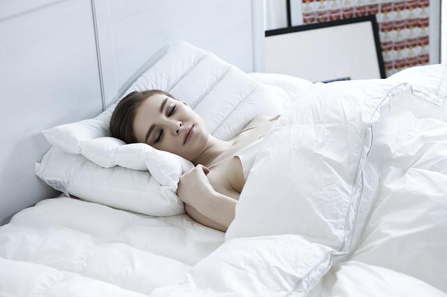 Žena s hnedými vlasmi spí v posteli.jpg