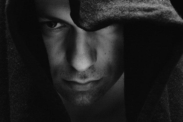 Muž zahalený v tmavej kapucni sa tvári smutne.jpg