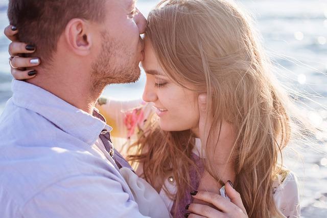 Muž bozkáva na čelo mladú ženu.jpg