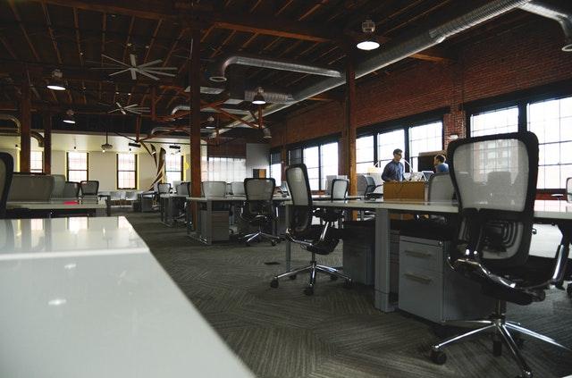 Veľká kancelária s veľkými oknami, bielymi stolmi a čiernymi stoličkami.jpg