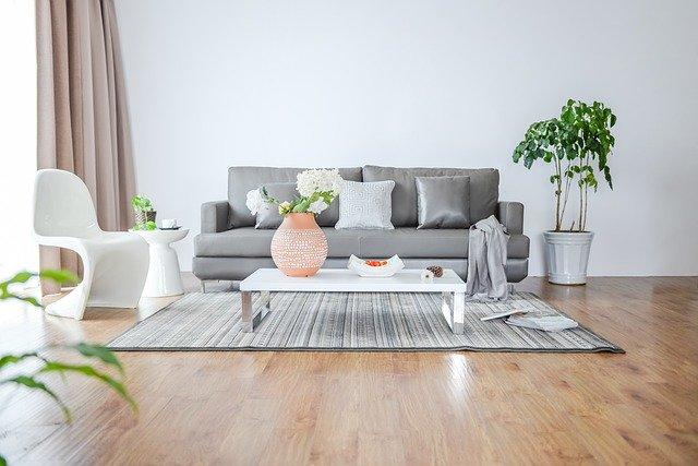 Moderne zariadená obývacia izba s hnedou podlahou a sivým gaučom.jpg